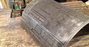 """Schwere Sache aus den 1970ern: eine rundgebogene Mater und mit Blei ausgegossene Druckform für den Rotationshochdruck einer Tageszeitung. Die Headline lautet: """"Kanzler: Eines Tages kommt 35-Stunden-Woche."""""""