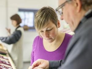 Uwe Steinacker zeigt einer Kursteilnehmerin das Stellen des Winkelhakens im Workshop Bleisatz und Buchdruck mit TypeSCHOOL in Dresden.