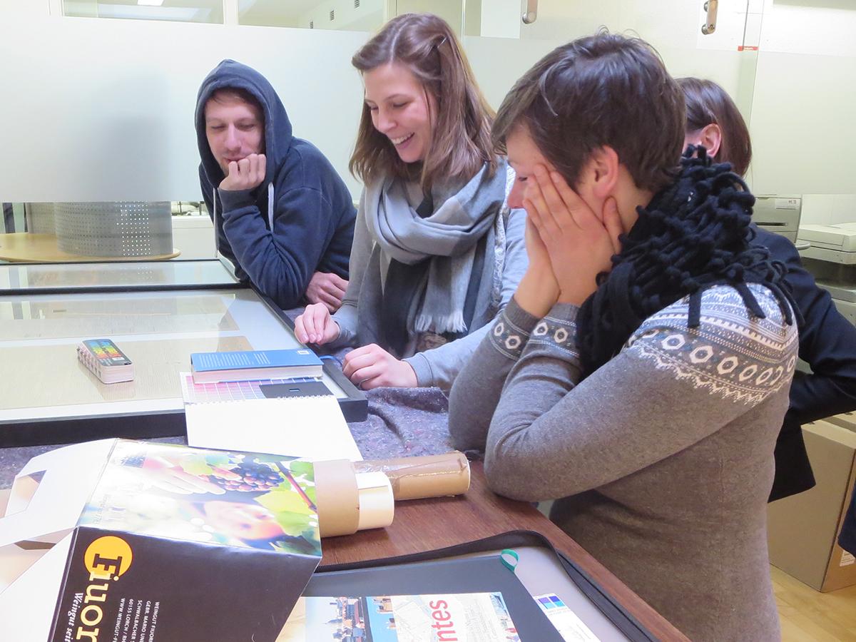 Teilnehmer beim Workshop zur Print-Produktion bei der praktischen Anwendung von Farbfächern.